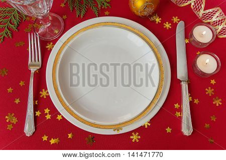 Christmas table in red and golden colors beautifully served luxurious tableware: porcelain plates and silverware decorated with Christmas balls candles and confetti; top view flat lay; overhead view