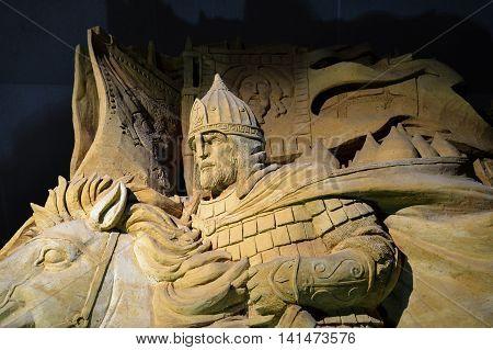 Warrior in armor on horseback. Sculpture of sand.