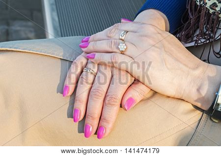 Well-groomed hands of fifty-year-woman in her lap during the relaxation