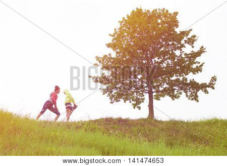Two fit young women friends exercising on the hill. Active healthy lifestyle and outdoor workout concept