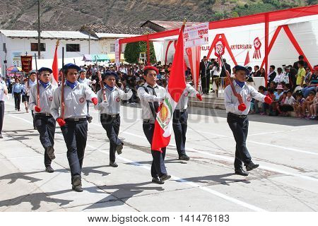 Magdalena Cajamarca Peru - July 25 2016: Young men with Peruvian flag march in town festival in Magdalena Cajamarca Peru on July 25 2016