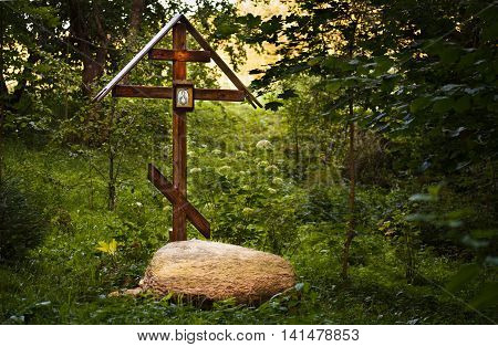 Worship cross with an icon in the woods near the holy spring