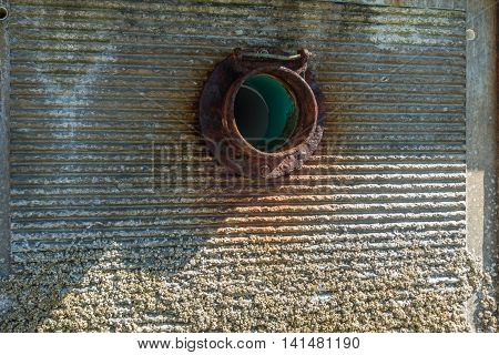 A rusted fitting encircles a sewer pipe exiting a wall.
