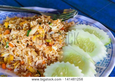 fried rice with crab and cucumber slice on a plate. Thai local food