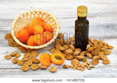 Apricot oil from apricot kernels in a brown bottle, apricot seeds around it and fresh apricots in a basket on wooden table