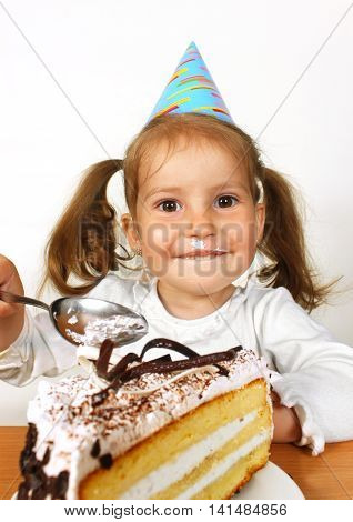 Portrait of smeared little girl with birthday hat eating cake