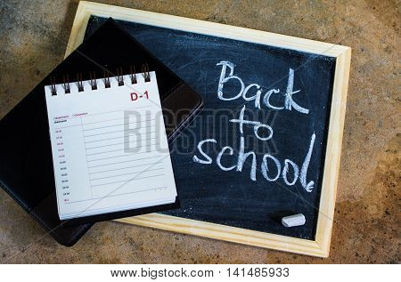 Back to school concept with chalkboard and notepad