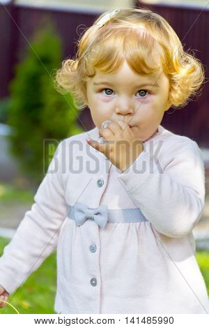 Portrait of cute baby girl with curly blond hair