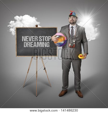 Never stop dreaming text with holiday gear businessman and blackboard with text