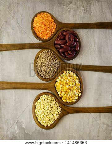 Wooden spoons with different organic grains on vintage background.Top view