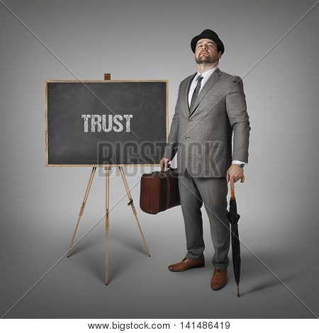 Trust text on  blackboard with businessman holding umbrella and suitcase