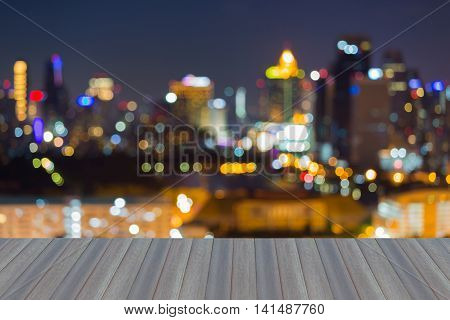 Opening wooden floor, Abstract blurred lights city downtown background
