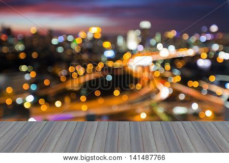 Opening wooden floor, Night blurred lights, city road interchanged and office building background