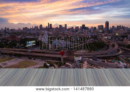 Opening wooden floor, Beauty of sunset sky over city downtown background and road interchange, long exposure