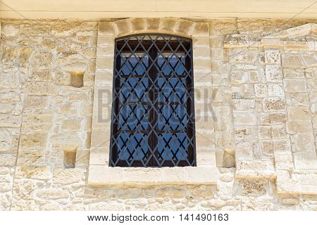 wooden window with iron lattice on ancient stone wall
