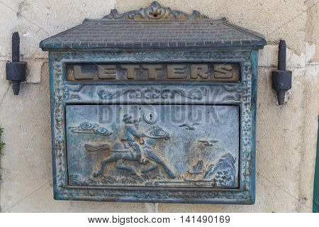 vintage iron letterbox decorated with carved picture on the wall