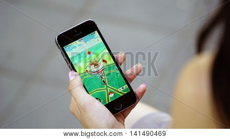Samara, Russia - August 6, 2016: woman playing pokemon go on his iphone. pokemon go multiplayer game with elements of augmented reality.