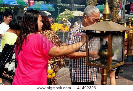Bangkok Thailand - January 25 2013: Elderly Thai man and a young woman lighting incense sticks from a flaming bronze brazier at the Thao Maha Brahma Erawan Shrine