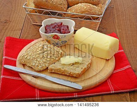 wholemeal bread roll with butter and jam on cutting board