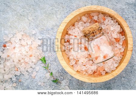 Closeup Himalayan Pink Salt In Wooden Bowl And Bottle  With Thyme Leaves On Stone Background. Himala