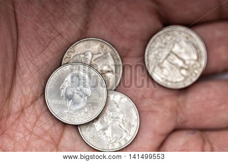 Four american quarters coins in a hand