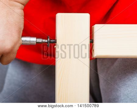 Human hand assembling wood furniture using screwdriver. DIY enthusiast. Home improvement.