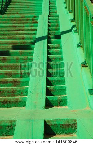 Green concrete stairs stairway with railing handrail on sunny day. Architecture. Urban scene.