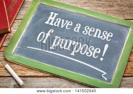 Have a sense of purpose advice or reminder on a slate blackboard with a white chalk and a stack of books against rustic wooden table
