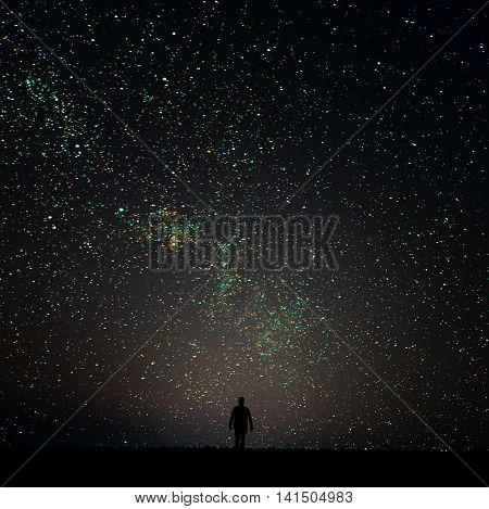 Silhouette of man looking at the stars. The man is on the horizon at night.Man desires guess looking at the stars.