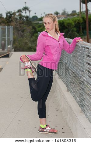 Blond athlete in pink jacket stretching her quads while looking straight.