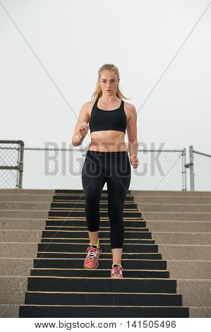 Intense female athlete in black tights descending stadium stairs.