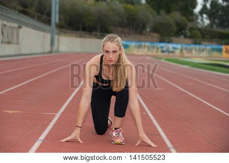 Sprinter in black tights crouched on the track.