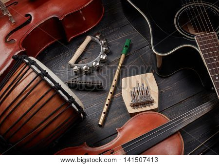 Set of musical instruments on dark wooden background: guitar, violin, harmonica, cello and others. Top view