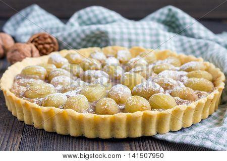Homemade shortbread dough grape tart with walnut praline horizontal closeup