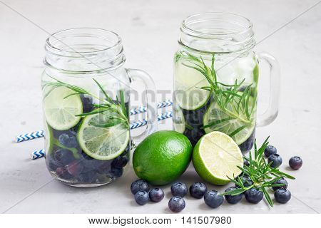Healthy cold infused water with fresh blueberry lime and rosemary horizontal