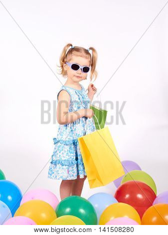 Shopping child. little girl holding shopping bags.Multi-colored balloons. Isolated on white background