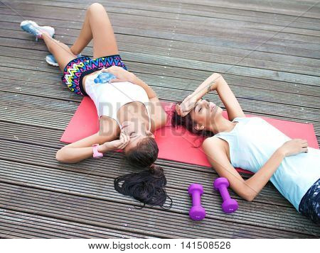 Two fit young women friends lying down tired after workout exercising in a park. Active healthy lifestyle concept