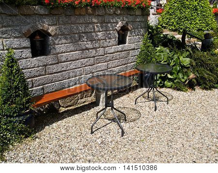 Landscaped backyard with beautiful garden furniture with tables and a wooden bench