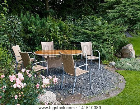 Landscaped backyard with beautiful garden furniture table and chairs in lush green area