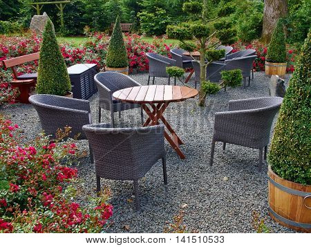 Landscaped backyard with beautiful garden furniture tables and chairs in lush green area