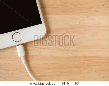 CHIANGRAI THAILAND -JULY 28 2016: Top view image of the Apple iPhone 6 charging with Lightning USB Cable on the wooden table on July 28 2016 in Chiangrai Thailand.