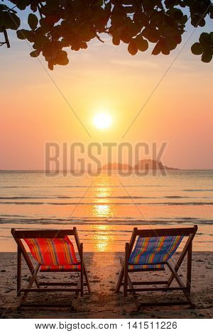 A couple of sun loungers on the beach during sunset.