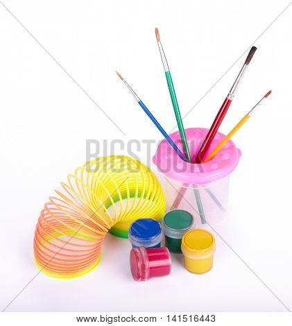 Multi-coloured gouache, paintbrushes in a cup and toy on a white background. Concept for Back to school