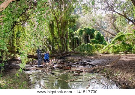 GWELUP,WA,AUSTRALIA-JULY 5,2016: People exploring at the lush, overgrown Secret Garden with ravine in the Careniup Wetlands in Gwelup, Western Australia.