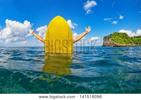Young happy surfer girl with spreading hands sit on surfing board and has fun. Healthy lifestyle people water sport lessons swimming activity in summer surf camp on family beach vacation with child