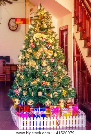 Decorating Christmas tree x-mas interior hotel. Christmas tree with presents
