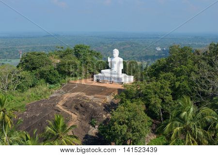 View of the old sculpture of a seated Buddha from the top of mount Aradhana Gala (the Rock of Invitation). The mango plateau, Mihintale, Sri Lanka
