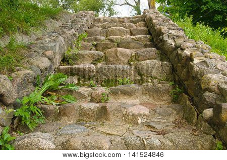 stone staircase leading upstairs . Rustic style .