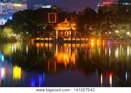 HANOI, VIETNAM - DECEMBER 13, 2015: View on the temple of the jade mountain on Hoan Kiem lake in night illumination. Historical landmark of the city Hanoi, Vietnam