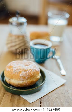 Bismarck Donut With Coffee On Wooden Table For Breakfast